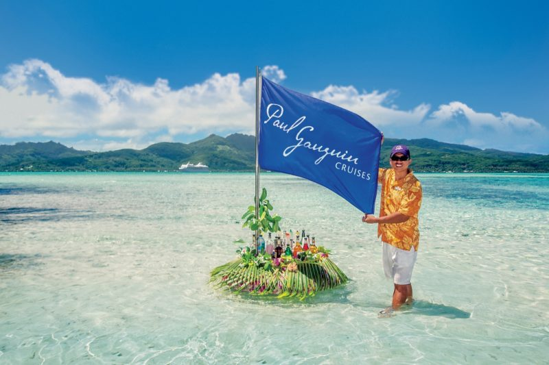 Paul Gauguin flag and crew member on a beach PR image