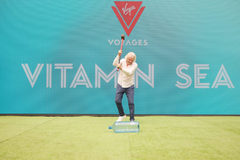 Richard Branson taking sledgehammer to plastic water bottle to market Virgin Voyages sustainable cruise option